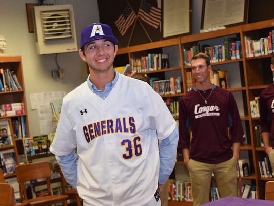 Grant High School baseball player Clayton Noakes smiles as he tries on an LSUA jersey and hat after signing to play at LSUA.