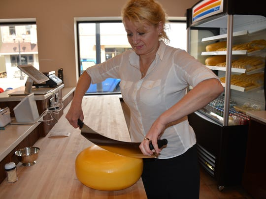 Olga Wakker cuts a round of Gouda cheese in the new