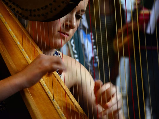 Ravenwood High School student Emily Stone plays harp