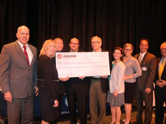 The Jay and Linda Grunin Foundation presented a check for more than $182,000 to fund innovative programs in each of Toms River's 19 schools. Superintendent David Healy (l), Board Vice President Loreen Torrone, Board President Robert Onofrietti, Jeremy Grunin, Jay Grunin, Kelly Filler, Tara Cunningham of the Jay and Linda Grunin Foundation, Assistant Superintendent  Marc Natanagara, and Assistant Superintendent John Coleman