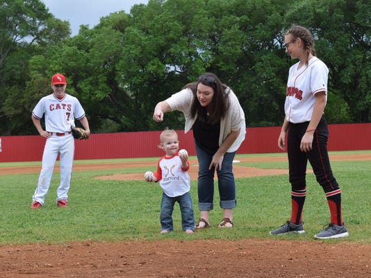 "Lacie Moore (third from left) points to son Stafford Moore (second from left), where he should throw one of the baseballs he is holding. Lacie Moore and Abbott Stafford (far right) are the daughters of the late Larry Stafford, former coach of the Glenmora High School Wildcats baseball team. On Tuesday, the baseball field that Stafford built at Glenmora High School was renamed ""Stafford Park."" His grandson Stafford threw out the first pitch in the park. Dylan Goree (7, far left) is a current member of the Glenmora HIgh School baseball team."
