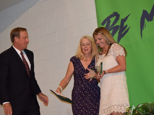 Gulf Breeze High swim star Tori Bindi shares laugh with Pensacola Sports president Jackie Brown and foundation director Rex McKinney after receiving the girls overall scholar athlete award at Tuesday night's banquet at Olive Baptist Church.