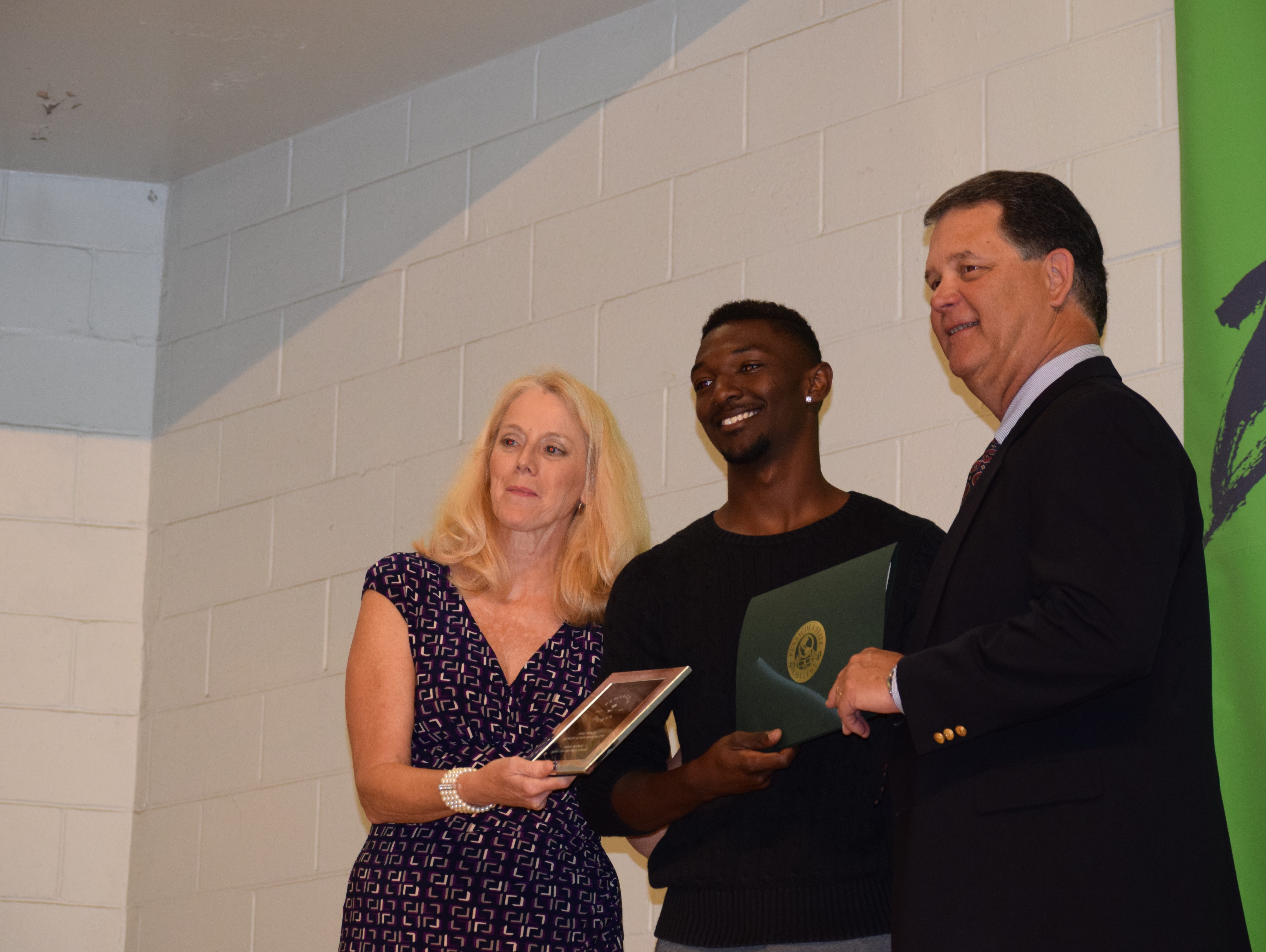 West Florida High's Javen Jackson is congratulated by Pensacola Sports president Jackie Brown and former president Bill Hamilton after Jackson received boys track award at the Senior Scholar Athlete Awards Banquet at Olive Baptist Church.