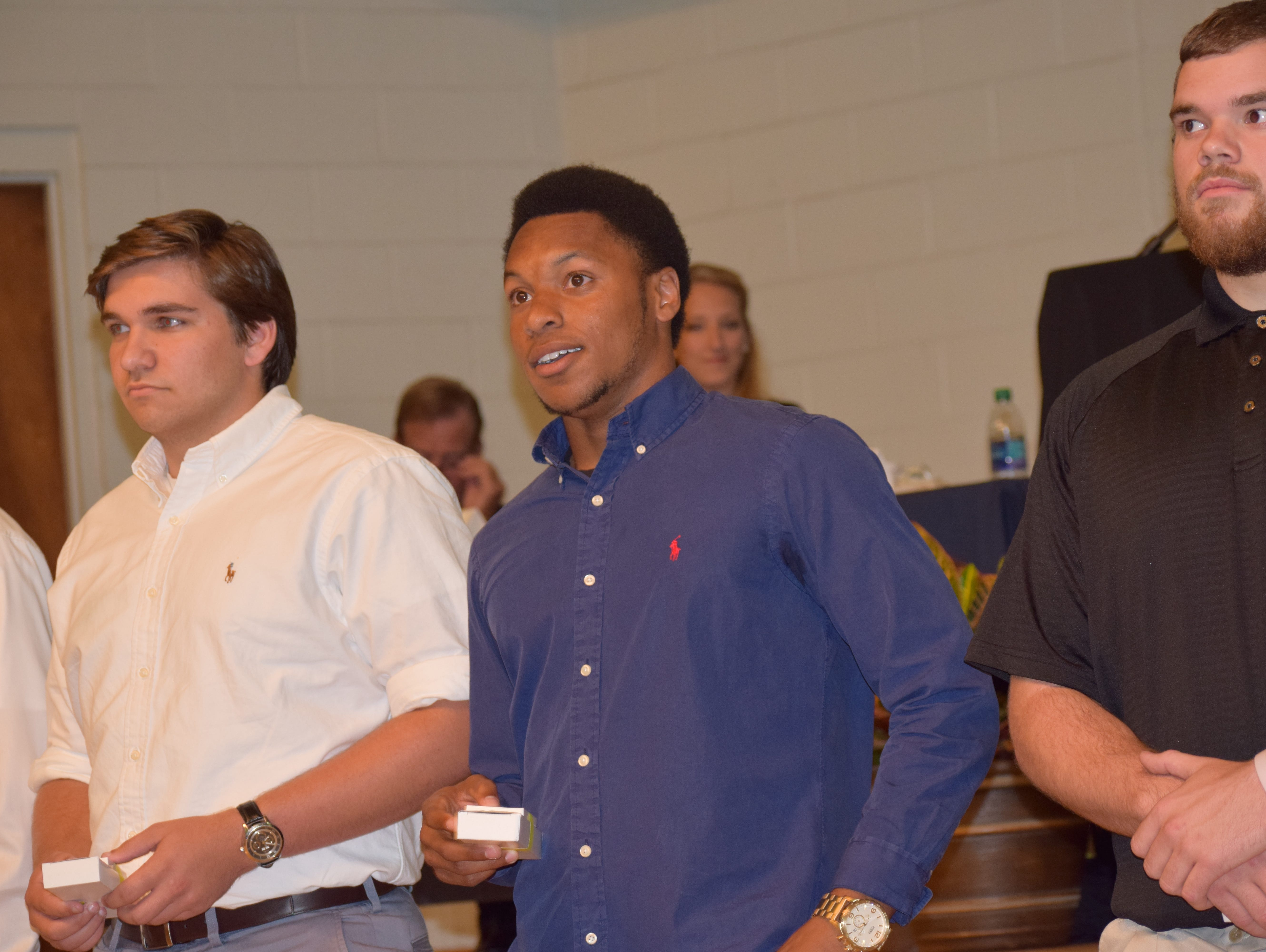 Navarre High's Michael Sandle (blue shirt) reacts when learning he was named the football award winner at Tuesday night's 37th annual Pensacola Sports Senior Scholar Athlete Awards Banquet