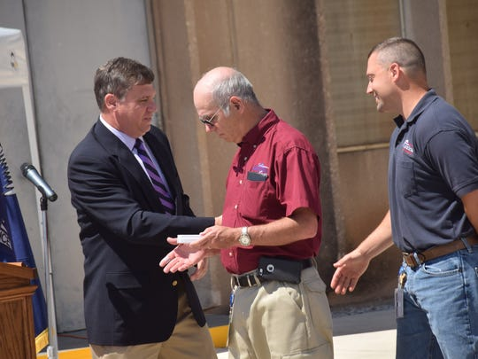 Alexandria Utilities Director Michael Marcotte (left) presents James Andrus (center), superintendent at the city power plant,  and Josh Foote, shift supervisor, with keys to the city during Friday's ceremony to dedicate seven new generators at the plant.