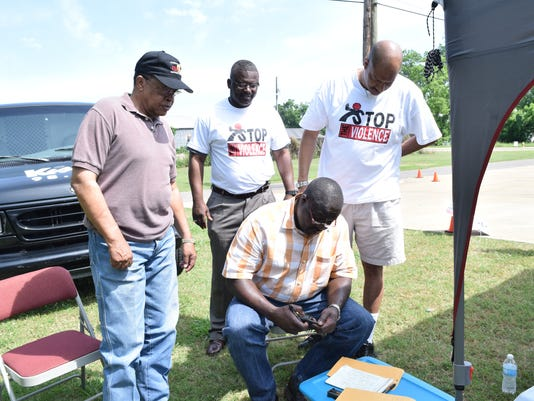 Detective David Rundell (front) checks a weapons turned in at a gun buyback hosted by Alexandria City councilman Ed Larvadain III (back, far right) and Rev. Randy Harris (back center), pastor of Mount Triumph Baptist Church, in the parking lot of Mount Triumph Baptist Church Saturday. With them is Rapides Parish Police juror Ollie Overton (far left) Harris and Larvadain are footing the bill for a gun buyback program. Those turning in serviceable weapons would get cash with no questions asked.