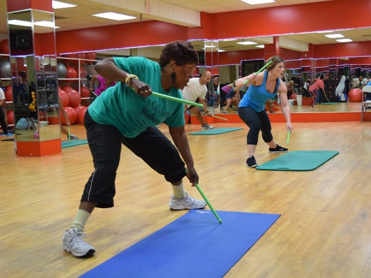 "Brittani Stout (far right), a Pound instructor at the Courtyard Health & Racquet Club in Alexandria, leads one of three Pound classes that the Courtyard offers. ""It's beneficial to the mind because you have to be alert,"" said Judy Franklin (far left), 78, a regular Pound participant ."