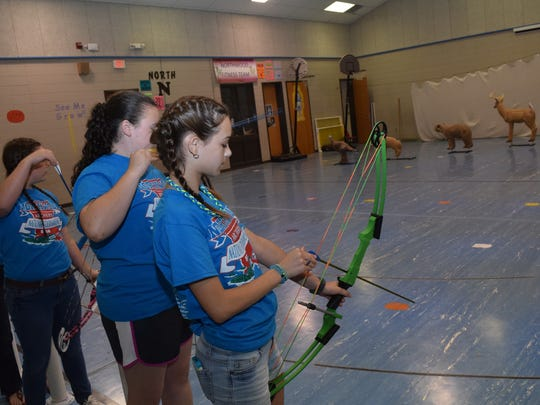 Northwood High School eighth-graders Ella Basco (back) and Kenzie Allen (front) are headed to a world competition in archery. They prepare to shoot at practice Tuesday.