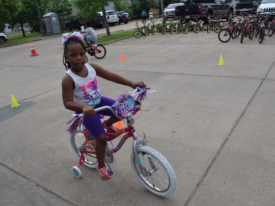 """Kailee Granvle, 5, takes her new bike for a spin Thursday at Laborde Earles Law Firm in Marksville. The Laborde Earles Law Firm gave away 231 children's bikes and helmets to children in the Lafayette and Central Louisiana areas as part of their """"Bike It Forward"""" program, which promotes community involvement, child safety, child health and well-being."""