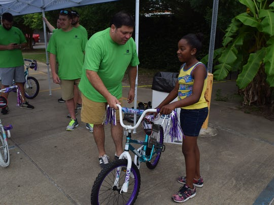 """Digger Earles (left), a partner at the Laborde Earles Law Firm, shows Kyasia Hills her new bike Friday at Laborde Earles Law Firm in Marksville. The Laborde Earles Law Firm gave away 231 children's bikes and helmets to children in the Lafayette and Central Louisiana areas as part of their """"Bike It Forward"""" program, which promotes community involvement, child safety, child health and well-being."""