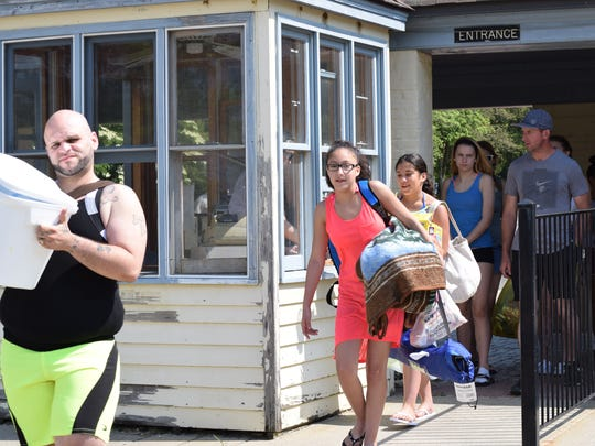 Jorge Rivera of Camden, Danielis Rivera, 12, of New Castle, Del., and Jocelyn Rivera, 10, also of New Castle, Del., enter Parvin Grove on opening day for their traditional Memorial Day visit at the park. Photo/Jodi Streahle