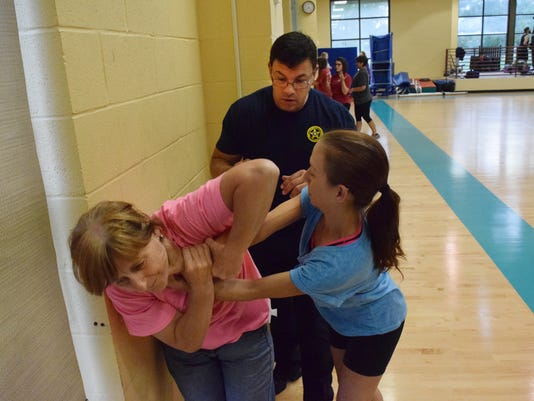 Tim Stanley (back), a deputy with the Pineville City Marshal's Office for Wards 9, 10, and 11, watches Cookie Tuma (left) and Angela Moore as they practice a chokehold escape. Sarah Smith, Pineville City Marshal for Wards 9, 10, and 11, said the marshal's