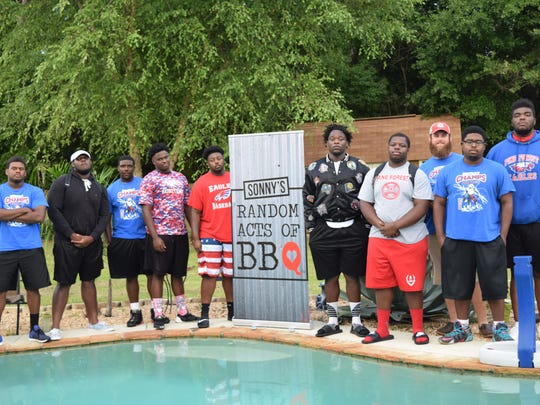 Pine Forest defensive line coach Lee Burt (third from right with hat) and his Eagles defensive linemen, who gathered at Burt's home.Sunday for surprise party organized by Sonny's BBQ.