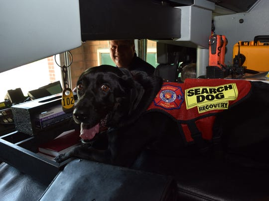 Nitro, a human remains detection dogs partnered with Alexandria Fire Department Capt. Jeff Tarver (back), has his spot in the fire truck where he rides when they are out on a call.