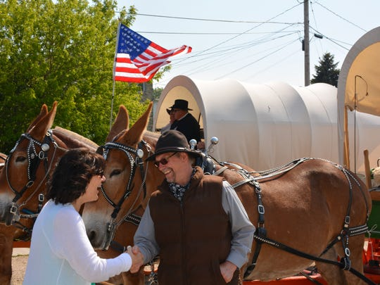 Kewaunee Mayor Sandi Christman greets David Holschbach, wagon train member, in downtown Kewaunee on June 10.