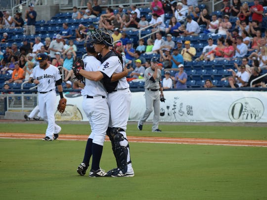 Blue Wahoos catcher Kyle Skipworth celebrates with reliever Alejandro Chacin after the Blue Wahoos 3-2 win in Saturday's first game.