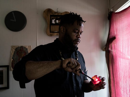 Asadullah Muhammad lights a candle in his bedroom on