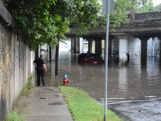 A Binghamton police officer works Tuesday to assist a car stuck under the Glenwood Avenue underpass in Binghamton.