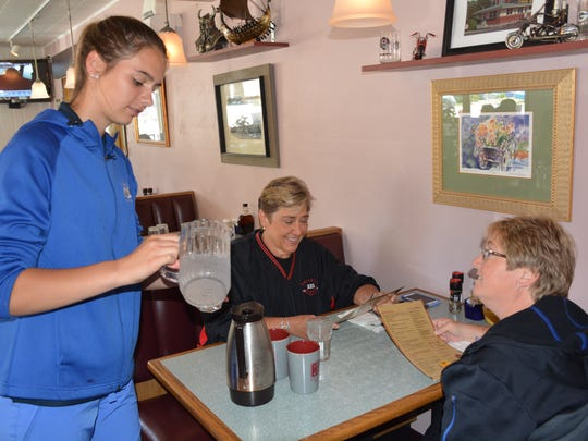 Madison Tesnow serves water at the Viking Grill to Beth Heuer, left, and Karol Fricke. She was 5 years old when the explosion occurred that leveled the old Pioneer Store across from the restaurant.