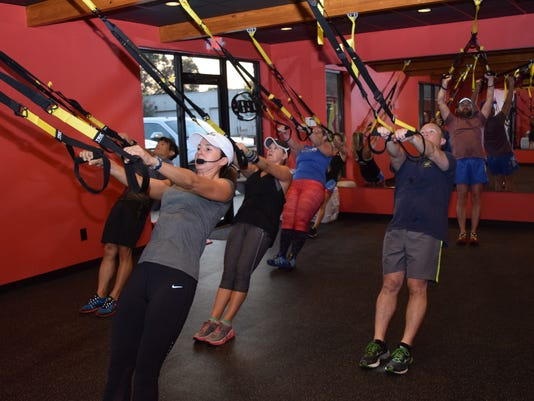 "Stacey McMickens, owner of FiXX Cycling and an endurance athlete coach, conducts a TRX suspension training class. ""What I Iove about TRX  is that in a very short amount of time, in a class, you can really increase overall core strength,"" she said.""While improving mobility and joint stability."""
