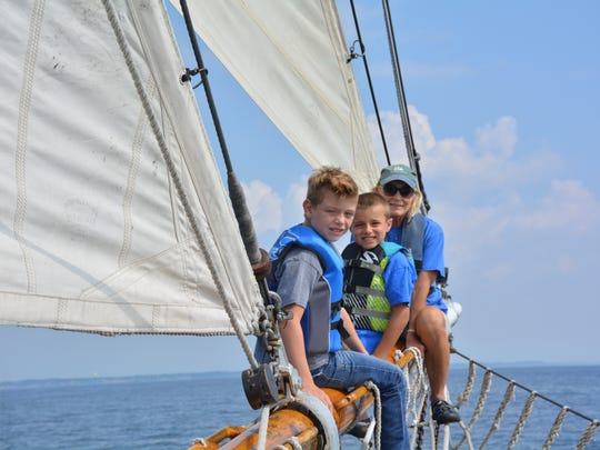 Lukas Jaensch, Dylan Haslam and crew member Barb Horning on the bow of the Tall Ship Madeline.