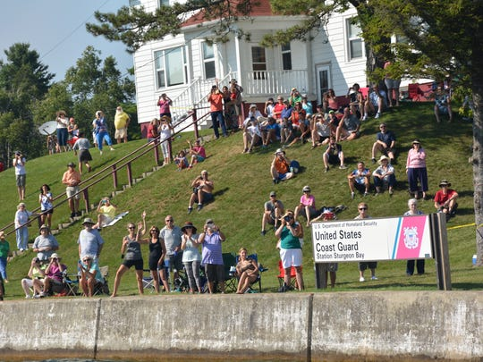 Spectators at the U.S. Coast Guard station watch the Tall Ships sail into the Sturgeon Bay Ship Canal..