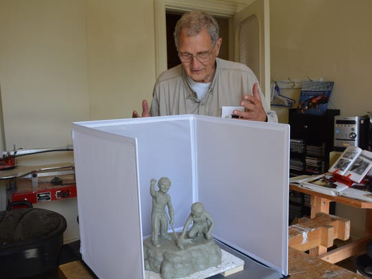 """""""We have a tourist and commercial fishing industry that should be preserved and that requires clean water,"""" says Dr. William Faller with a model of a sculpture of Native American boys fishing he is creating for the City of Kewaunee."""