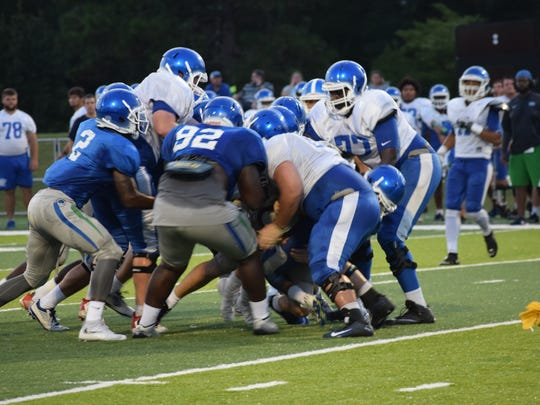 With a penalty flag in the air, UWF's defense swarms the ballcarrier in Friday night's scrimmage.