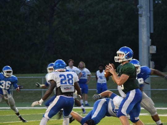 UWF quarterback Grey Jackson looks downfield as defenders close in on him during Friday's scrimmage.