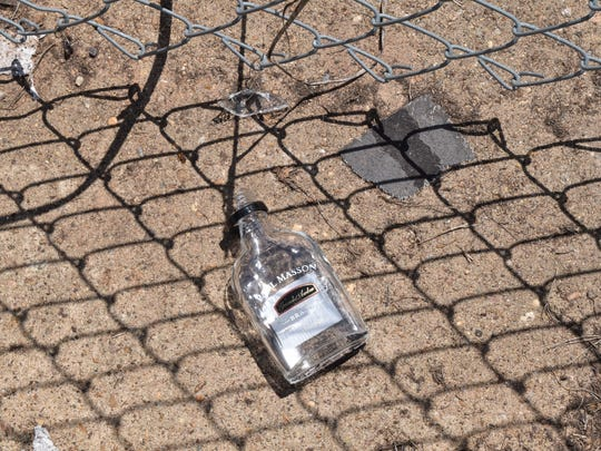Empty liquor bottles like this one are among the trash littering an area near Overton and Lee streets in Alexandria. Residents of that area are being asked to call police when they see littering, loitering and other crimes.