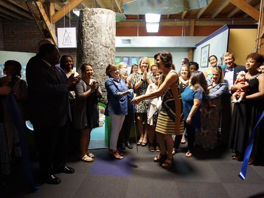 Melissa Saye of the Northeast Louisiana Children's Museum, center left, and Lynn Clark, director of the Northeast Louisiana Children's Coalition, center right, cut the ribbon on the new Baby Bayou play area at the Northeast Louisiana Children's Museum.
