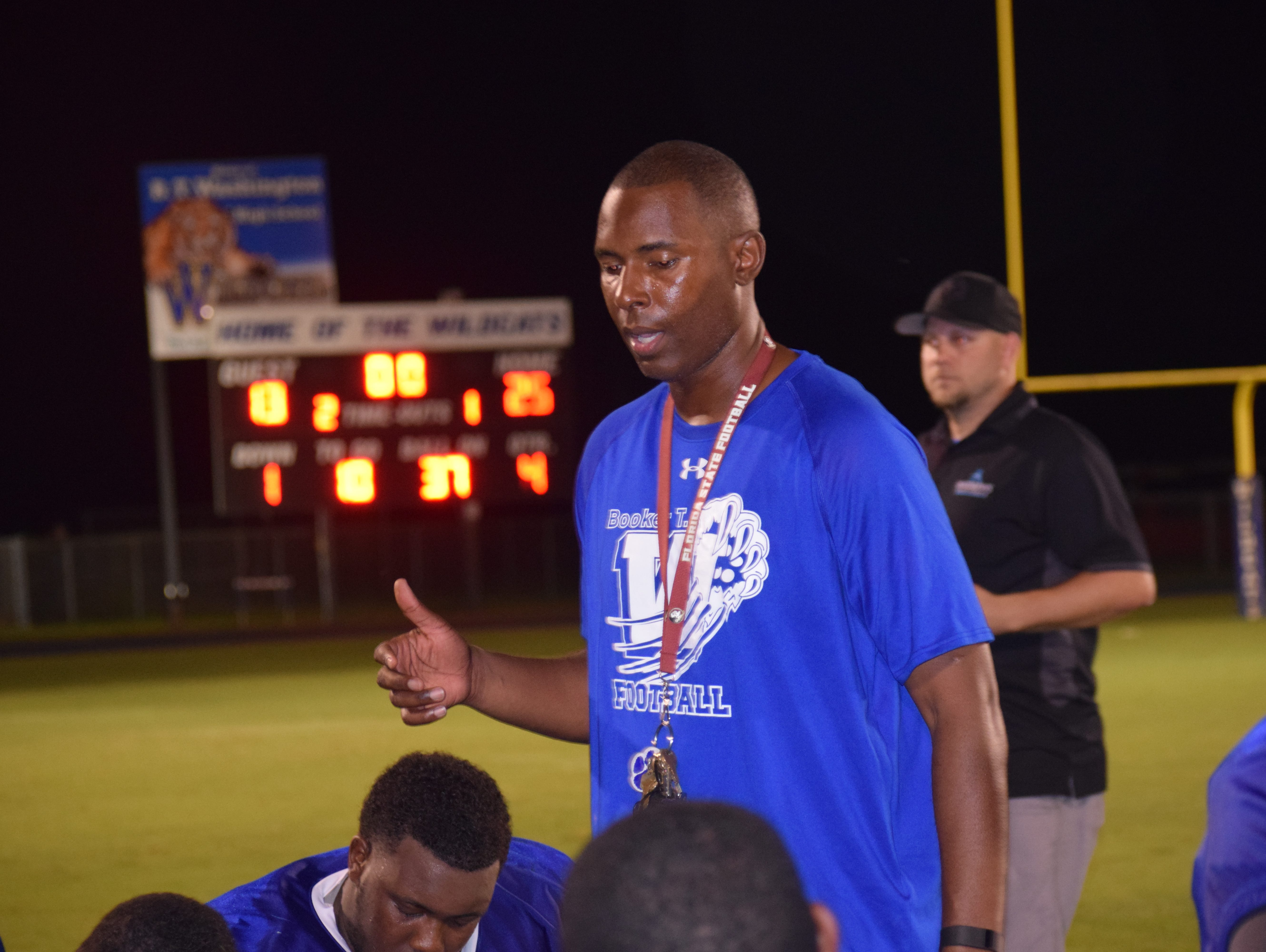 Washington High coach Charlie Ward meets with his players following season-opening win against Milton.