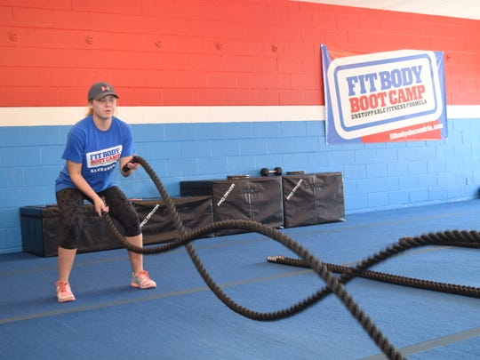 Tobi Soileau, general manager of Alexandria Fit Body Boot Camp, shows how quick waves are performed using battle ropes. The battle ropes can be used to work on the upper body, arms, legs and core depending on the exercise.