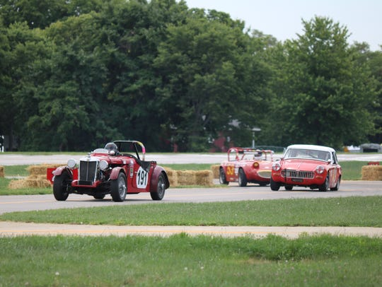 Vintage race cars pull around tight turns at the airport