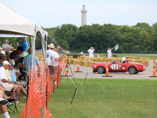 The checkered flag waves as the winning drivers pull into the 'FAN ZONE' at the Put-in-Bay Road Races Reunion.