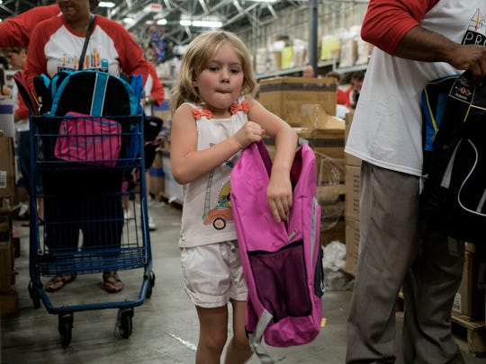 Madison Craig, 5, from Canton stuffs a backpack full of school supplies during the Project Backpack Detroit stuffing event on Friday, Aug. 12, 2016 at Meijer in Livonia.