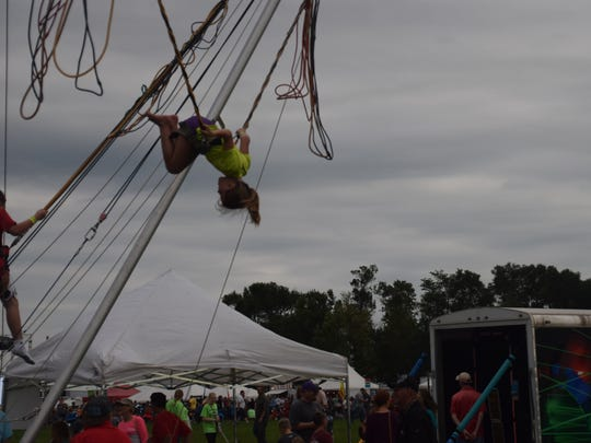 Kenzley Pater of Pipestone, Minn. spins upside down at Lifelight's kid's area on Saturday.