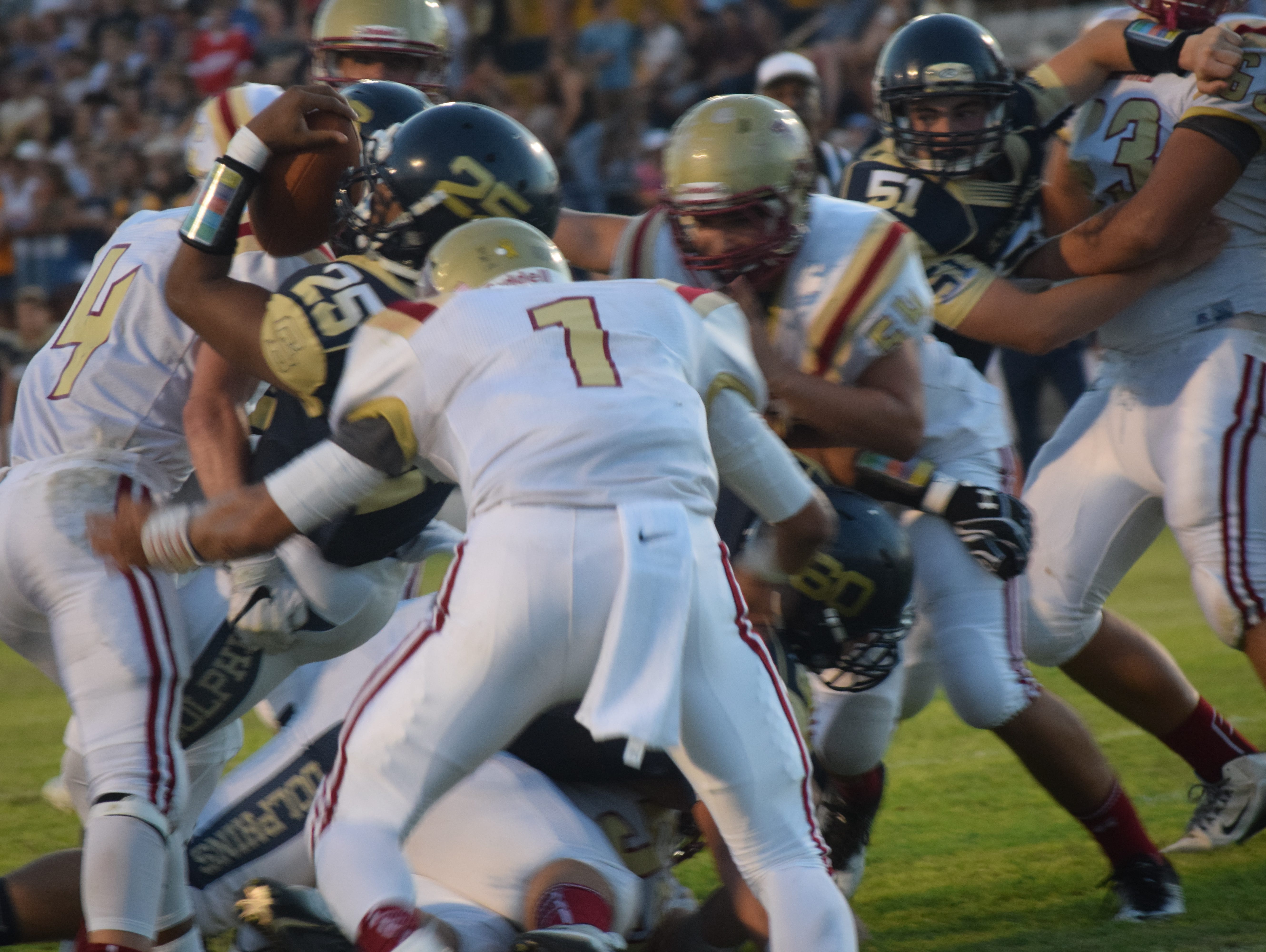 Gulf Breeze sophomore running back Carl Taylor (25) puts the ball over the plane of goal line to score the Dolphins first touchdown Friday night as Northview's Luke Ward closes in.