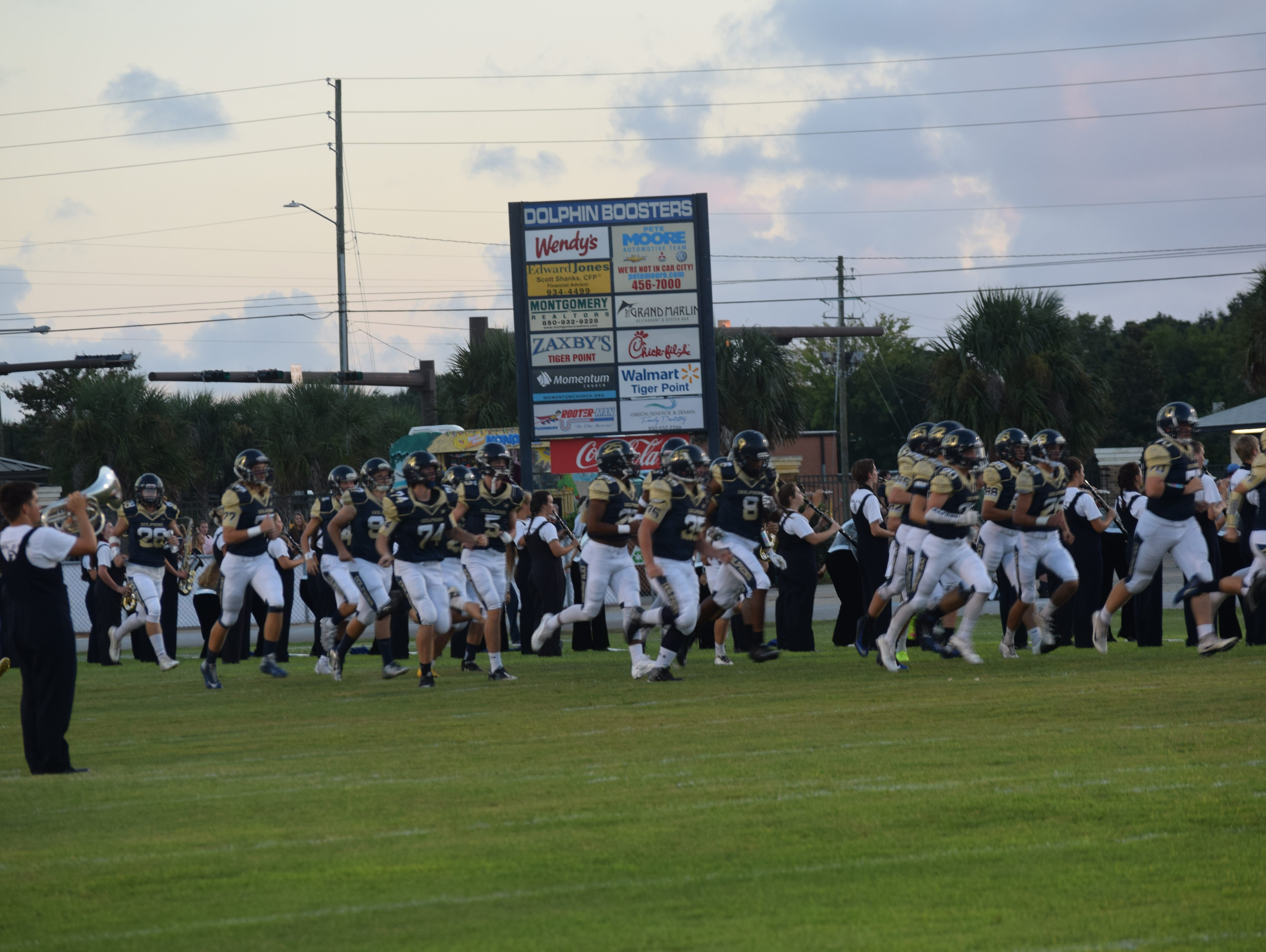 Gulf Breeze players race on the field Friday night prior to kickoff against Northview High.