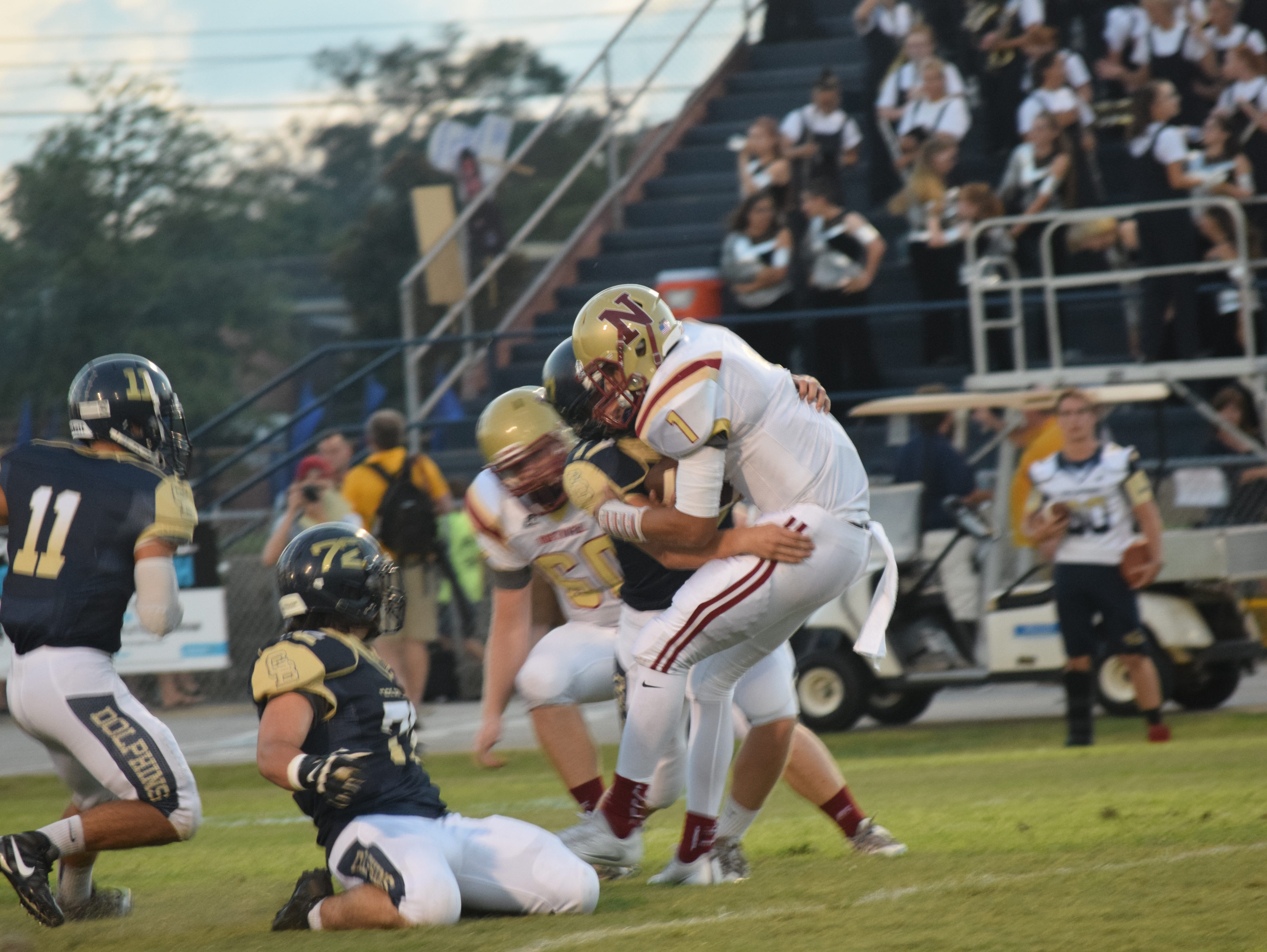 Gulf Breeze linebacker Will Sawarynski brings down Northview quarterback Luke Ward on a first-quarter sack Friday night in the Dolphins' 42-0 win against the Chiefs. .