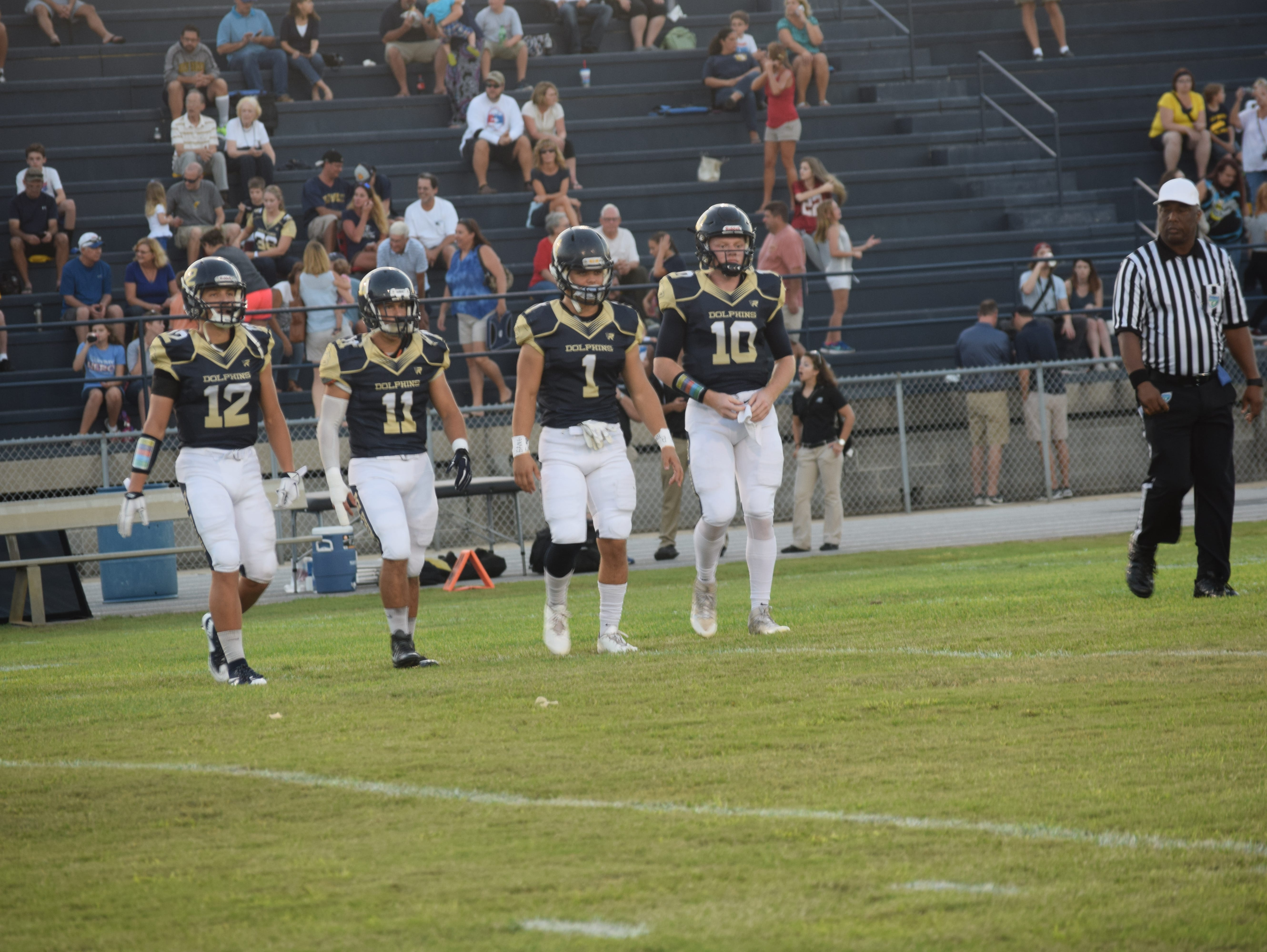 Gulf Breeze team captains Cole Sheppard (12), Ben Dobry (11), Logan Green (1) and Tyler Phelps walk out for opening coin toss Friday night before game against Northview.