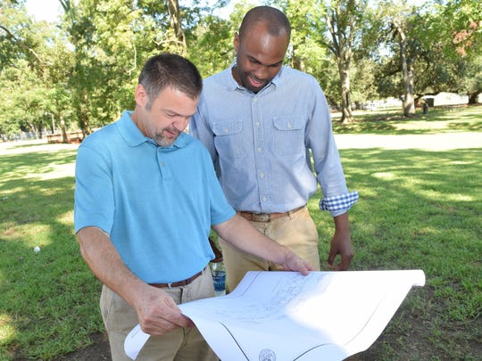 """Darren Green (left), landscape architect for the city of Alexandria, and Alexandria Community Services Director Daniel Williams look at plans for the dog park which will be located between Gilbert Street and Hynson Bayou. It will be called """"Hynson Bark"""" and is expected to open in early 2017."""