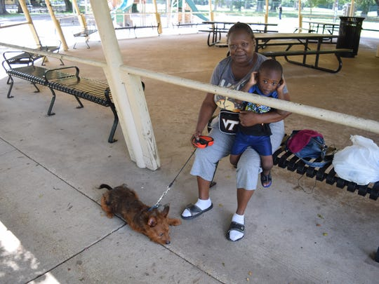 Joyce Roberson holds her nephew Brayden Taylor and holds the leash of her dog Buddy while visiting Alexandria City Park. She likes the city of Alexandria's plan to build a dog park across Masonic Drive from City Park.