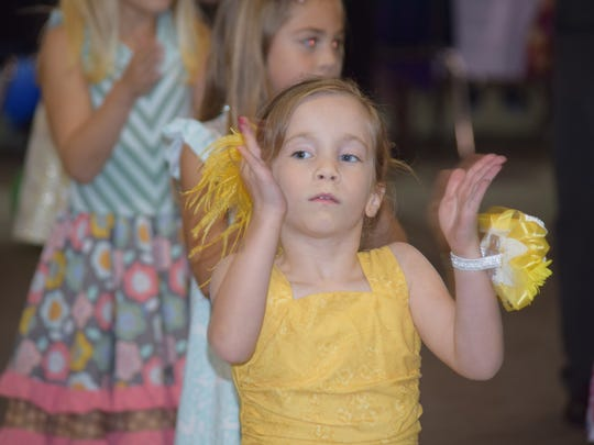 "Lily Moore,6, claps along to the ""Cha-Cha Slide"" at Old National Bank's eighth annual Daddy-Daughter Dance and First Mother-Son Dance."