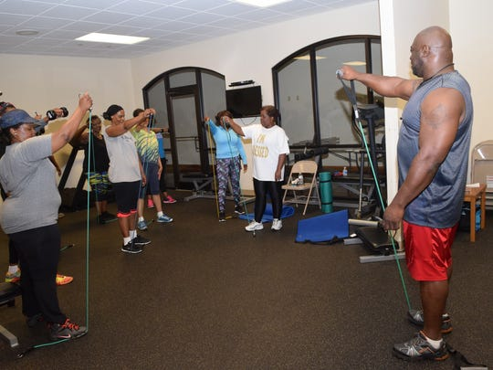 "Patrick Shaw (right), 48, started helping the students in Samantha Louie's class, ""Pain With a Purpose"" with strength training. He sees his duty as helping them build their mind, body and spirit. ""I'm motivated in spirit,"" he said. ""I look at everyone like a muscle fiber. We strengthen one another."" Shaw feels that the class can take the same motivation they learn out into the community."