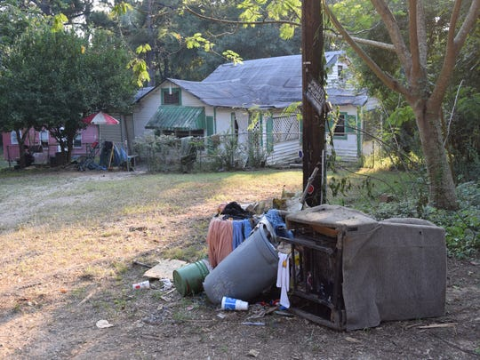 A discarded chair and other trash sit near a vacant residence along Bell Road in Pineville.