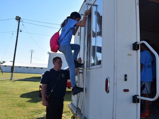 Fire Chief Chad Cullen assists students in learning how to escape a house in an emergency.