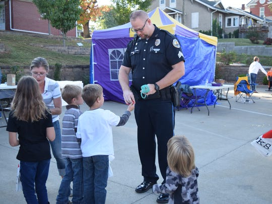 Police Officer Geoff Deibler hands out bracelets to the children at the Fall Family Fun event last Thursday.