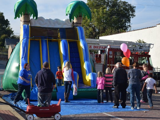 Guests line up to take a turn on the bouncy slides during Fall Family Fun.