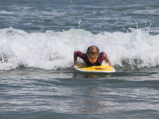 Charlie Cox, 6, braces herself as she catches a wave and prepares to pop up and surf. Although she was initially scared of trying a real surfboard, she was hooked after just one try.